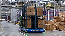 A fully loaded transport platform moves autonomously through a warehouse.