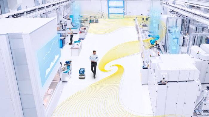 A man with a tablet is walking about in a production facility equipped with robots and mobile platforms. A yellow graphic element moves around the production area and symbolizes safe productivity.