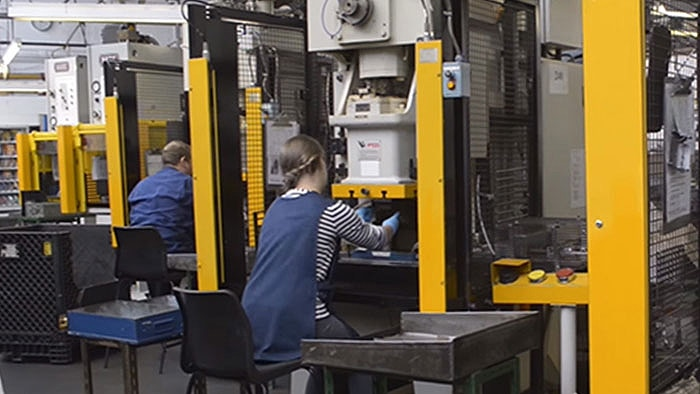 Two workers working at manual insertion presses.