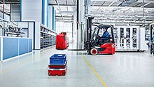 An AGC, AGV and a forklift move about in a production hall.